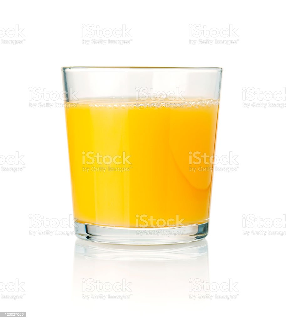 Tumbler glass of orange juice resting on a white surface stock photo