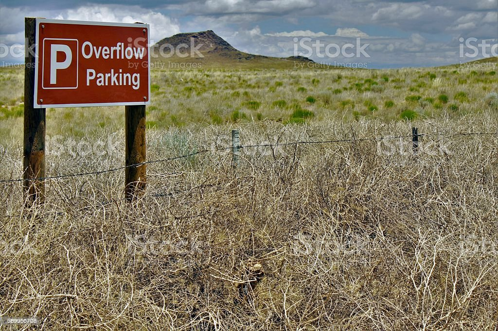 Tumbleweeds in front of Overflow Parking Sign stock photo