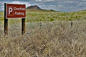 Tumbleweeds in front of Overflow Parking Sign