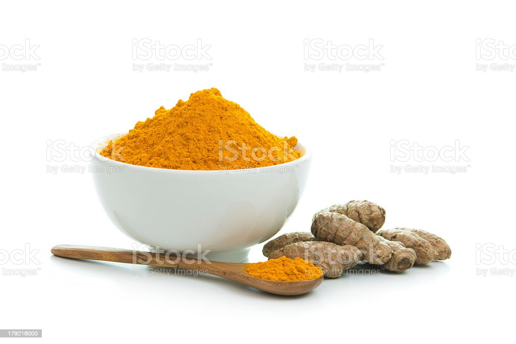 Tumeric powder in a white bowl with wooden spoon stock photo