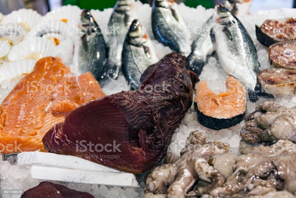 Tuna and Salmon on ice, waiting to be sold, in market stall stock photo