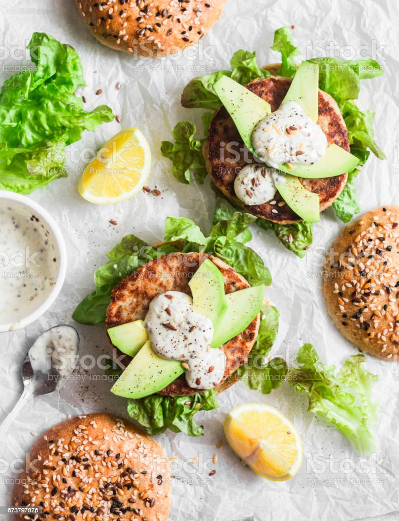 Tuna burger on a light background, top view. Burger with tuna, avocado and mustard sauce, delicious appetizer or snack stock photo