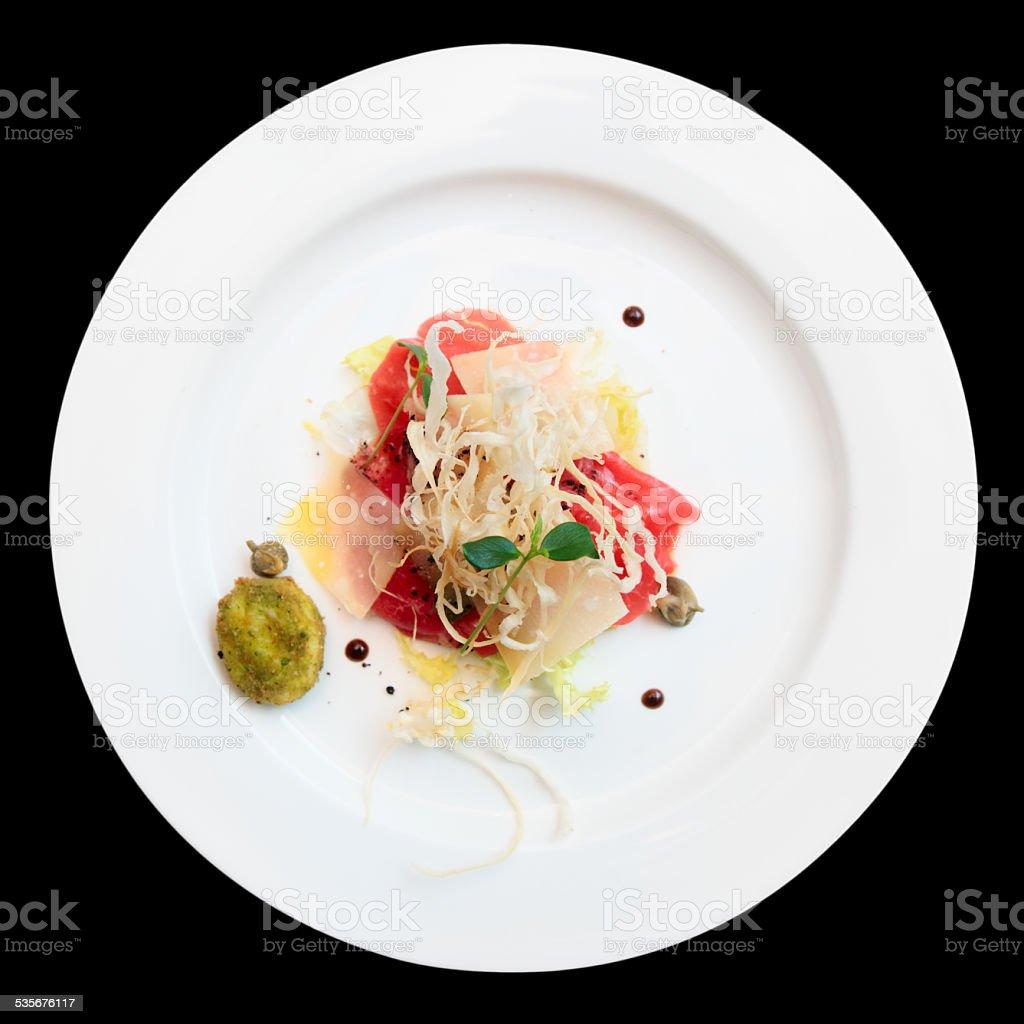 Tuna carpaccio on plate isolated over black stock photo