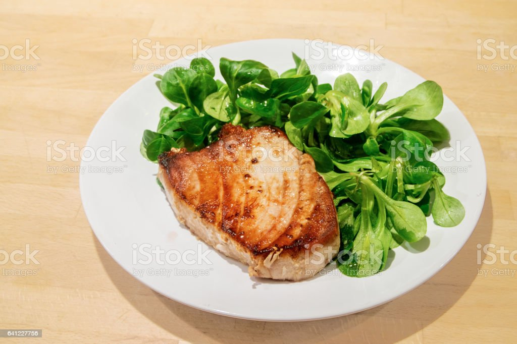 Tuna steak with salad on a white plate, wooden background stock photo
