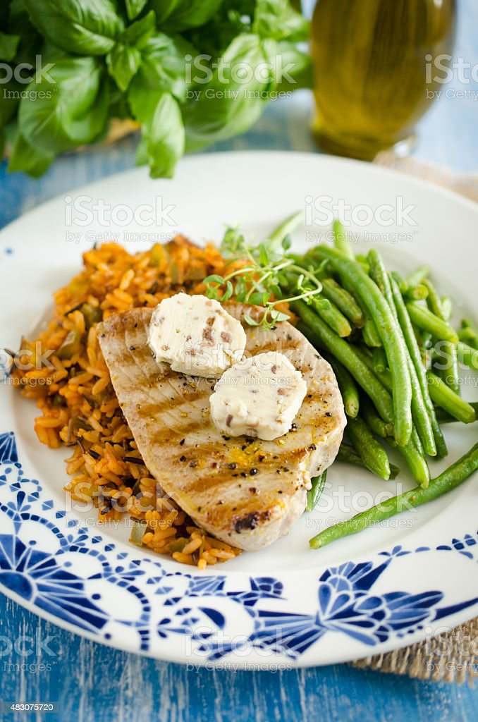 Tuna steaks with lemony anchovies butter and red pepper rice stock photo