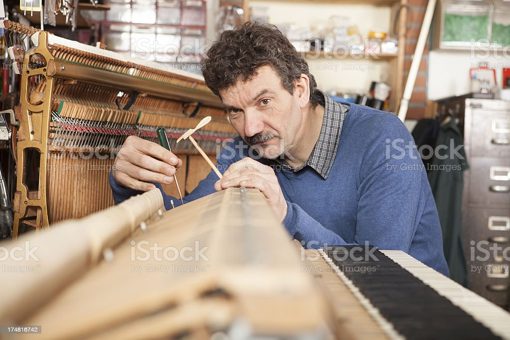 Tuning a piano royalty-free stock photo