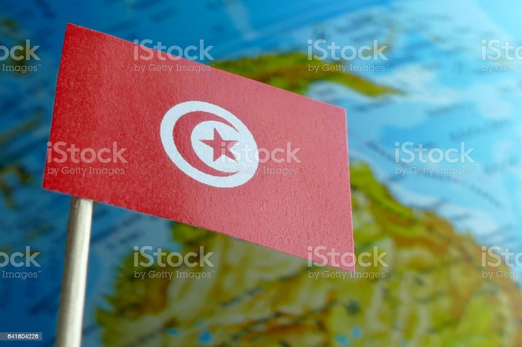 Tunisia flag with a globe map as a background macro stock photo
