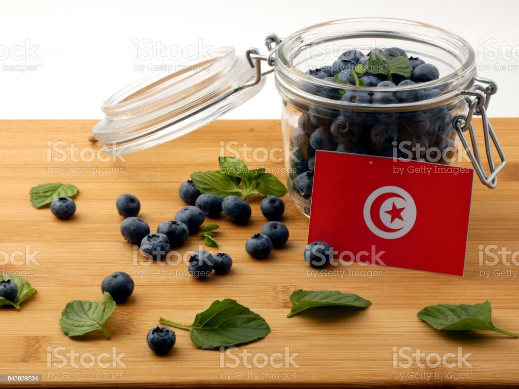 Tunisian flag on a wooden plank with blueberries isolated on white stock photo