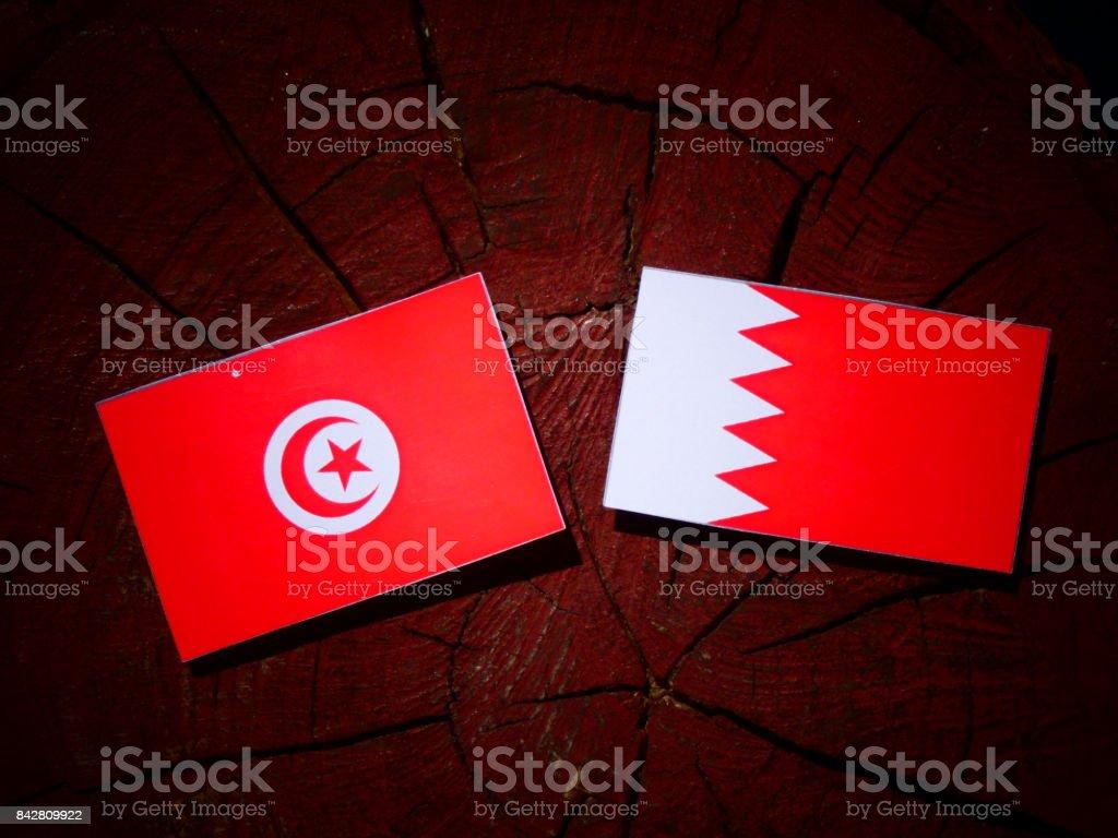 Tunisian flag with Bahraini flag on a tree stump isolated stock photo