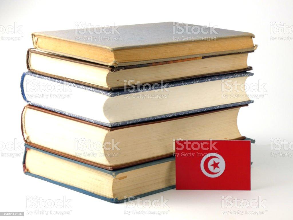 Tunisian flag with pile of books isolated on white background stock photo