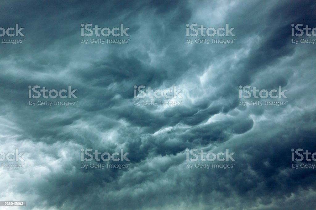 Turbulent storm clouds spreading across sky stock photo