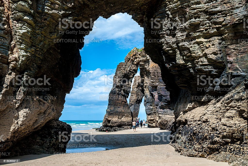 Turists under Natural rock arches Cathedrals beach stock photo