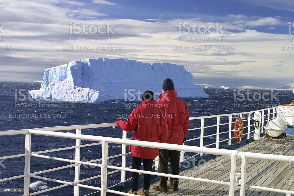Turists viewing iceberg, Antarctica. stock photo