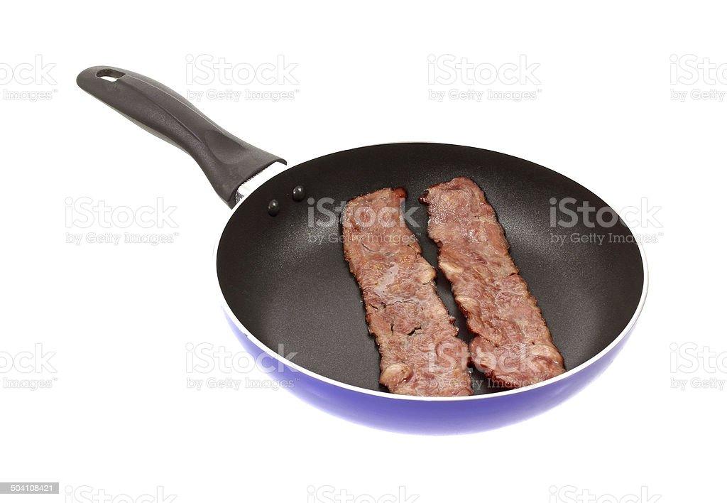 Turkey bacon in skillet stock photo