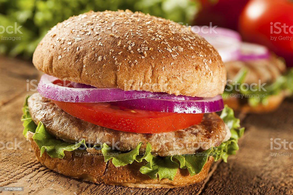 Turkey burger in a bun with tomato, lettuce and onion stock photo