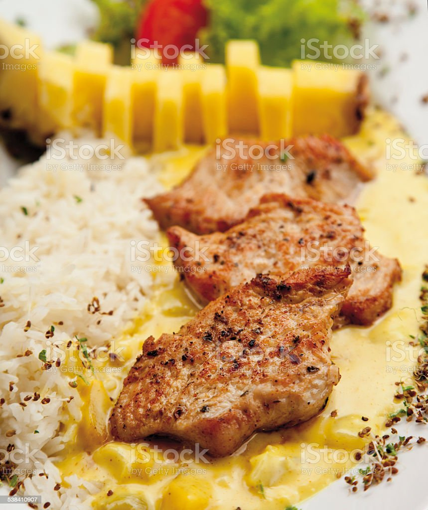 Turkey hen filet garnished with rice, pineapple and curry sauce stock photo