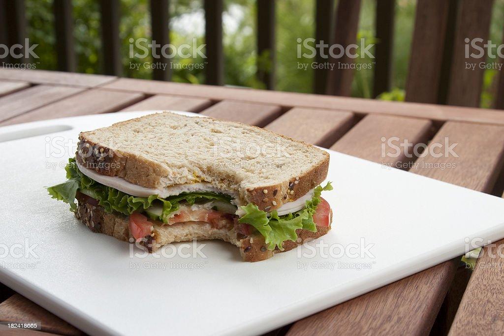 Turkey sandwich on wheat with a bite taken stock photo