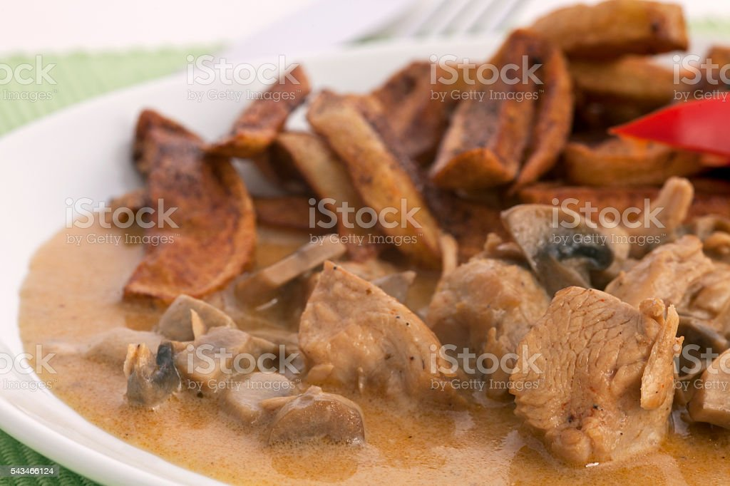 Turkey with mushrooms and french fries stock photo