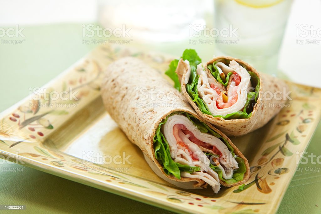 Turkey wrap with lettuce and tomatoes on a square plate stock photo