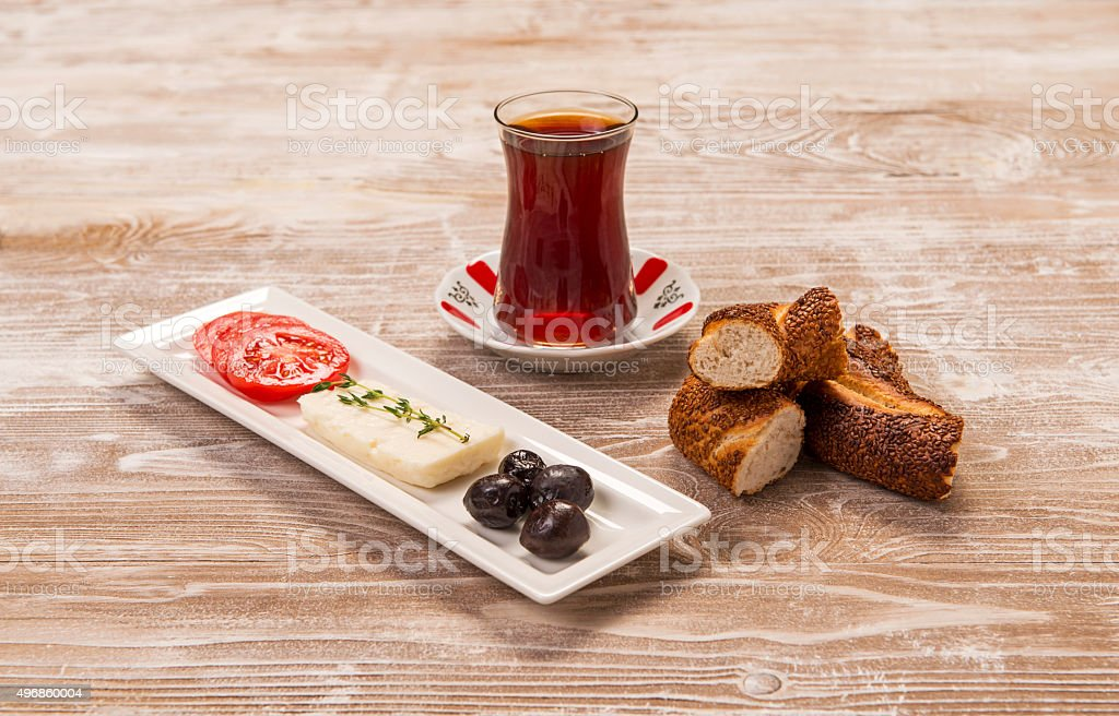 turkish bagel, simit, tomatoes and tea on wooden table stock photo