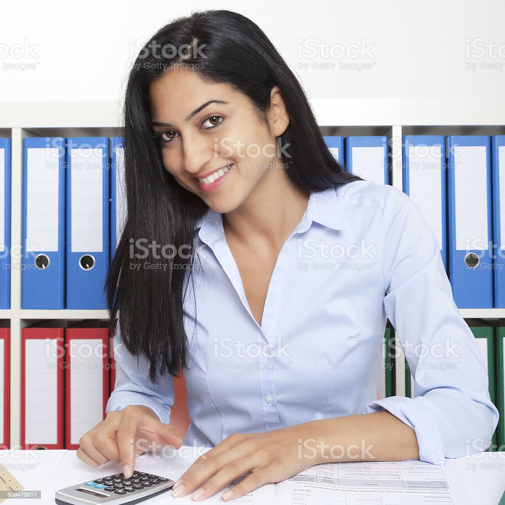 Turkish businesswoman working with calculator at office stock photo