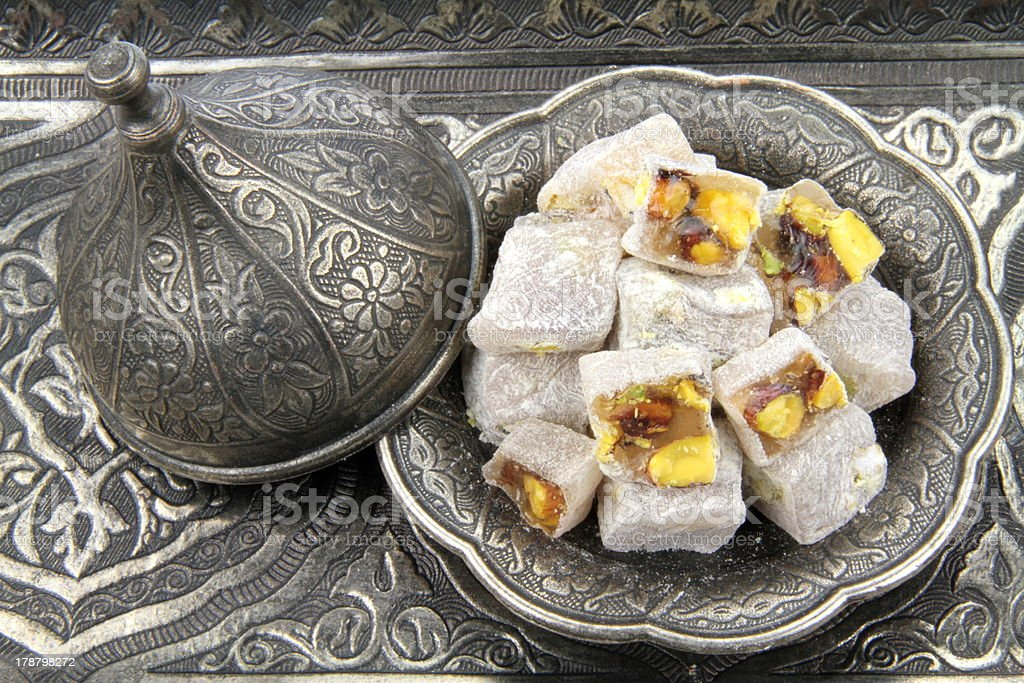 Turkish delight with  pistachio nuts on carved patterned metal plate. stock photo