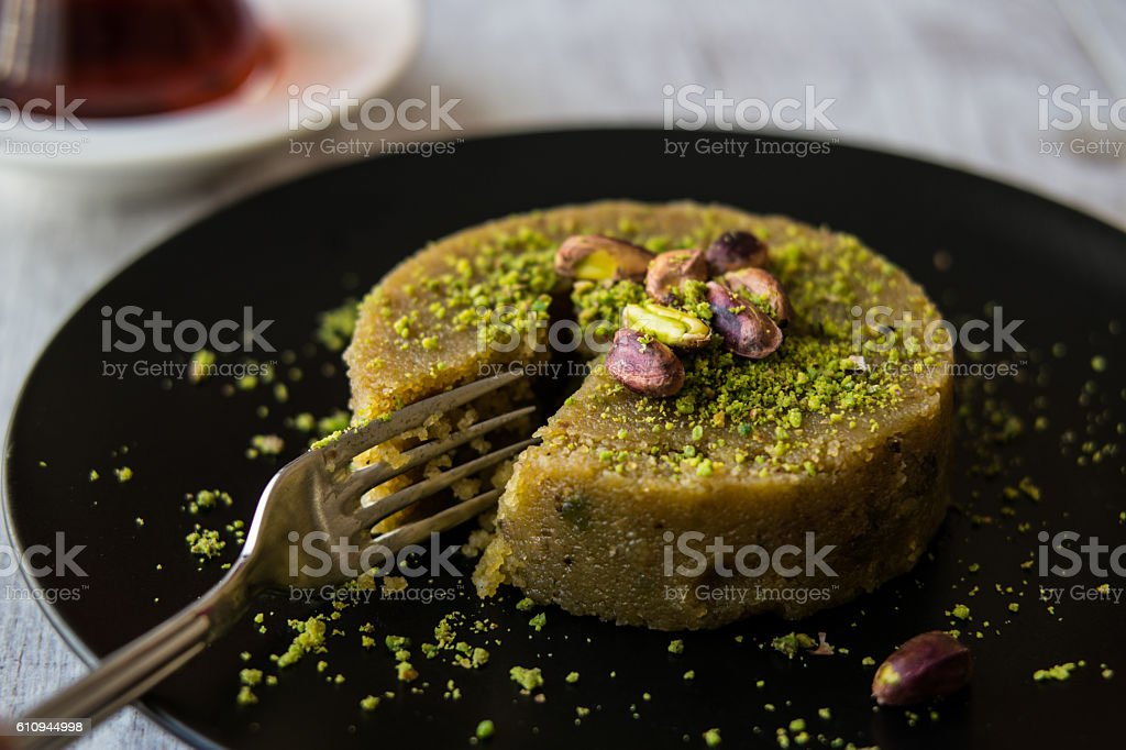 Turkish Dessert irmik helvasi with pistachio powder and tea. stock photo
