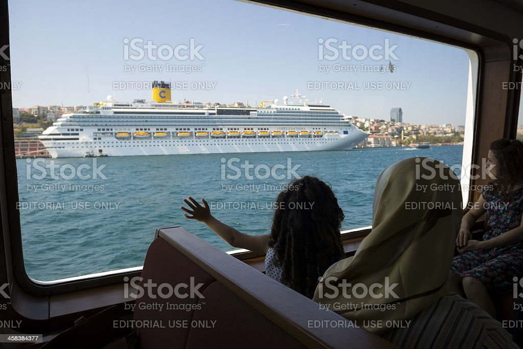 Turkish girl looking at Costa Fascinosa cruise ship in Istanbul stock photo