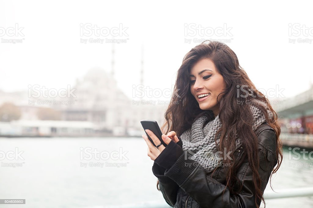 Turkish Girl Texting On Smartphone Outdoors In Istanbul stock photo