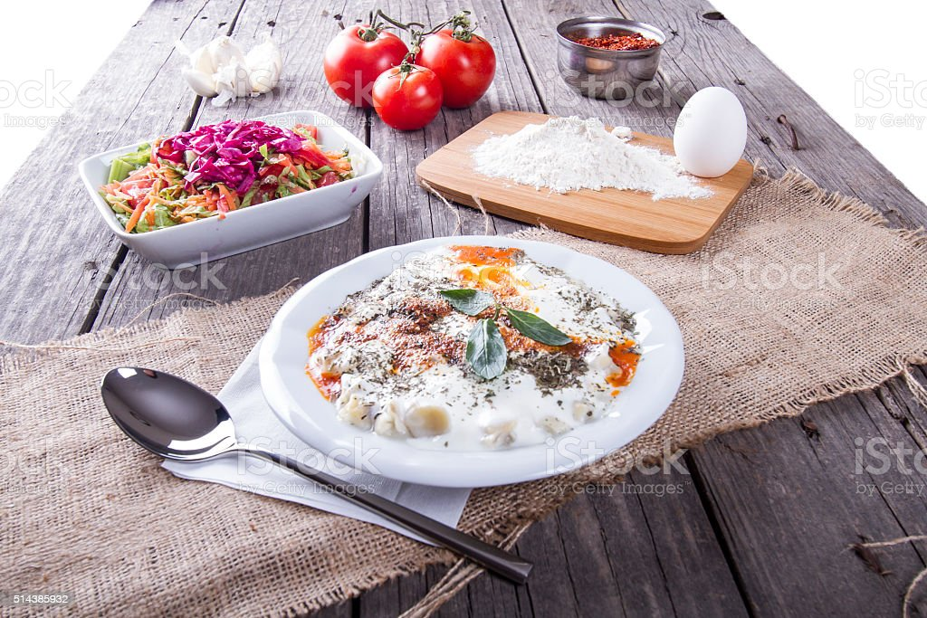 Turkish Manti on plate with red pepper, tomatoes sauce, yogurt stock photo