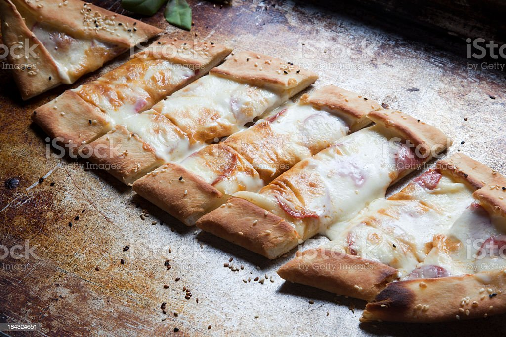 A Turkish pizza resting on a metal surface royalty-free stock photo