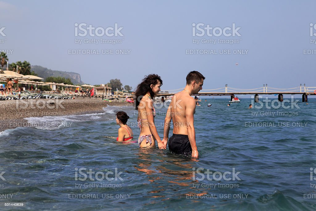 Turkish resort, Couple goes deep into the seawater holding hands stock photo