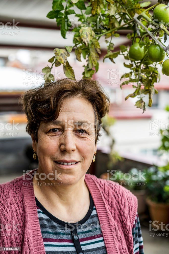Turkish Senior Woman Portraid with Greed Tomatoes stock photo