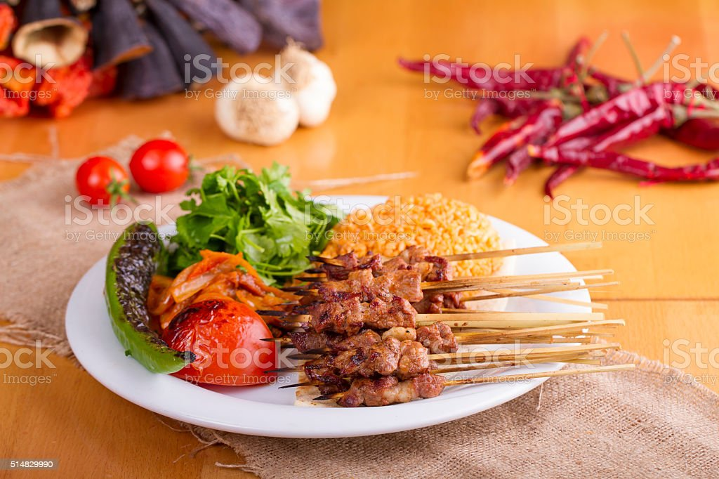 Turkish Sis Kebab in a plate on wooden and ayran stock photo