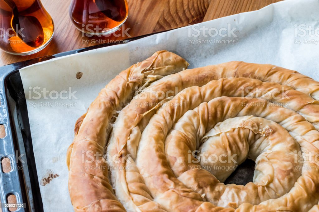 Turkish Tepsi Boregi / Round Borek in tray with tea. stock photo