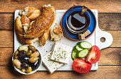 Turkish traditional breakfast with feta cheese, vegetables, olives, simit bagel
