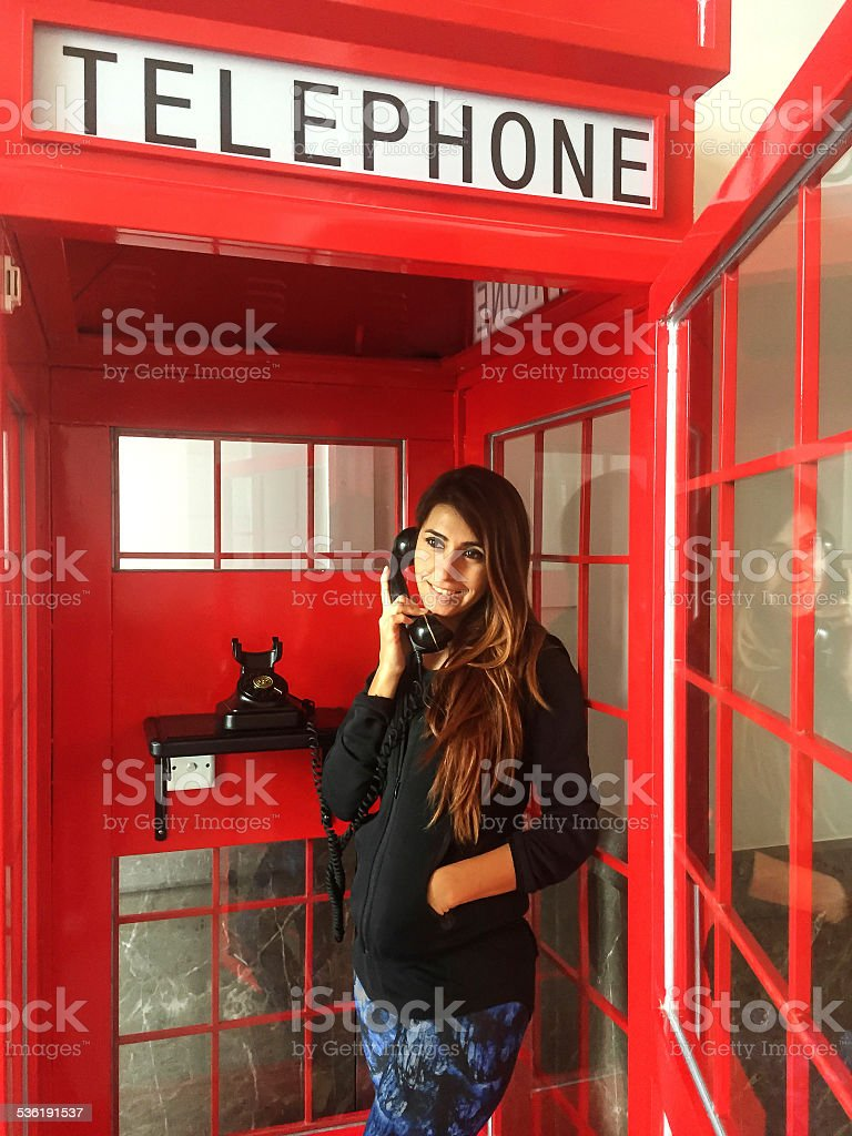 Turkish Woman in Red Telephone Booth stock photo