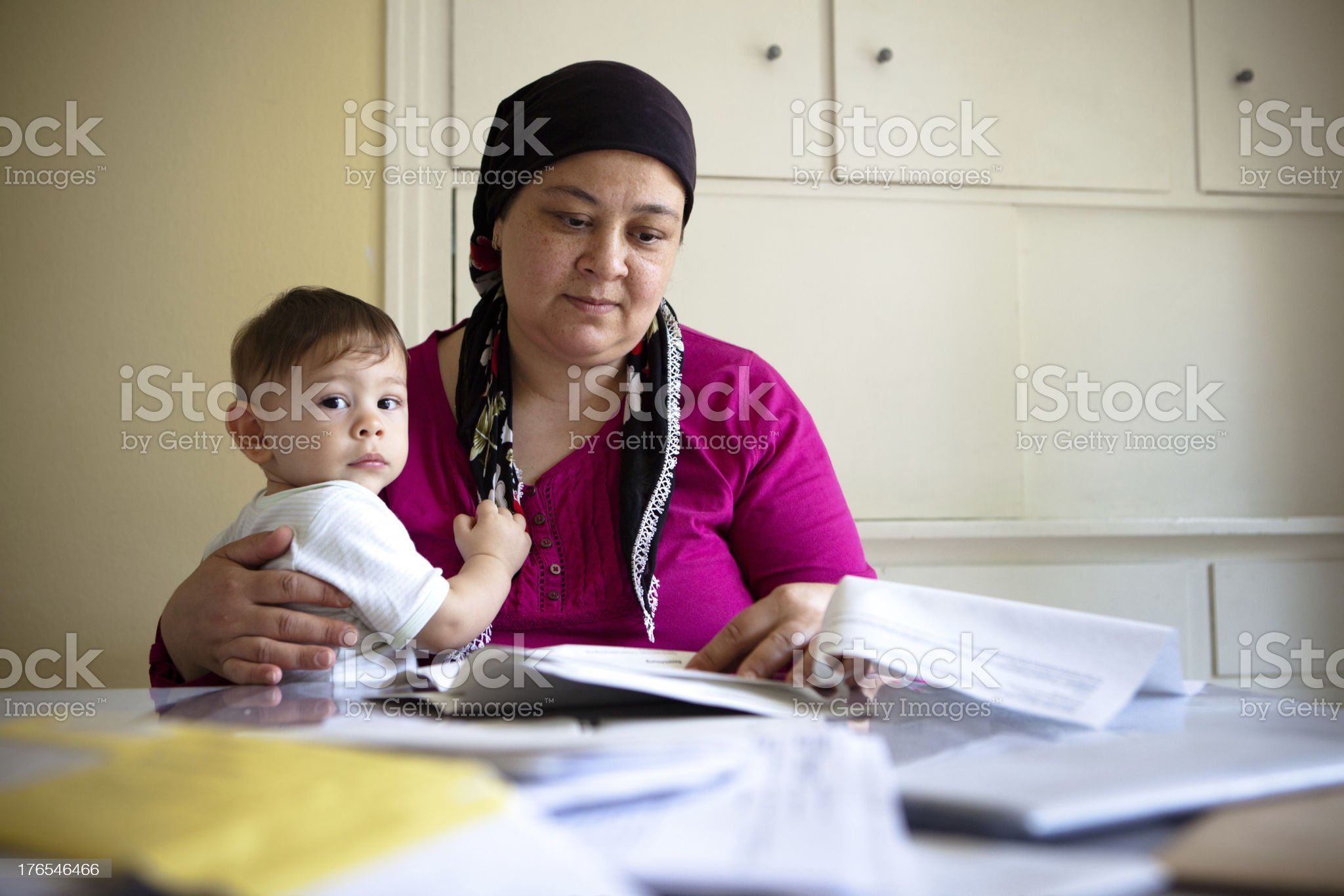 A Turkish woman sorting through paperwork looking helpless royalty-free stock photo