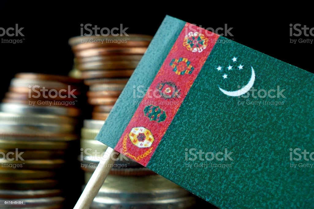 Turkmenistan flag waving with stack of money coins macro stock photo