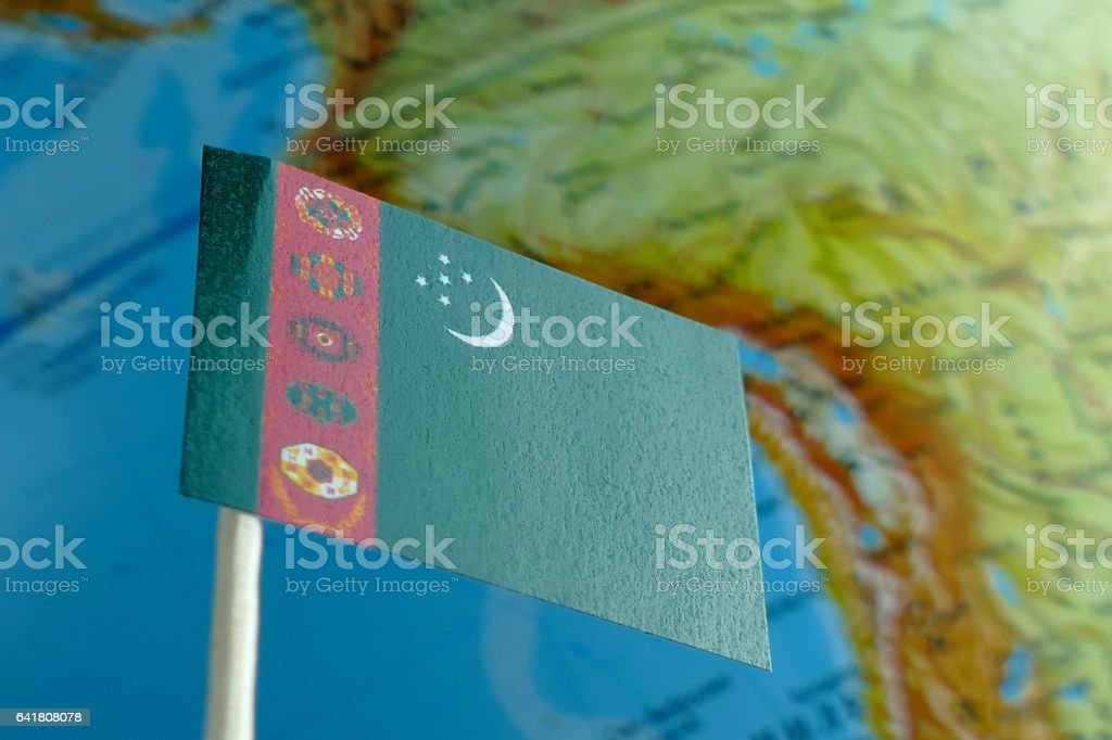 Turkmenistan flag with a globe map as a background macro stock photo