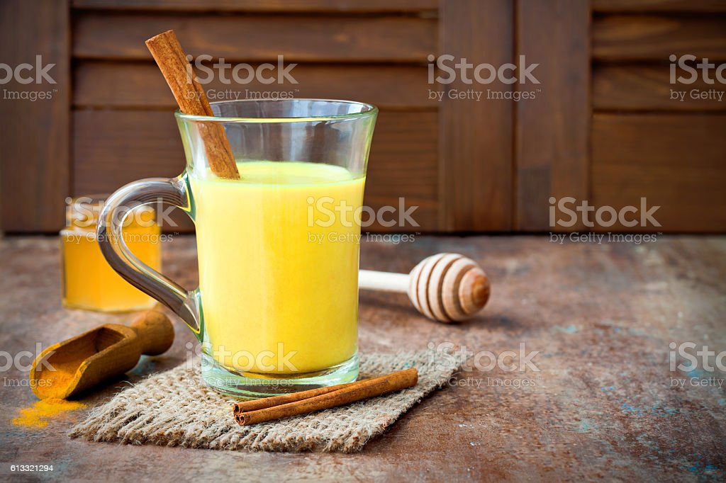 Turmeric golden milk latte with cinnamon sticks and honey stock photo