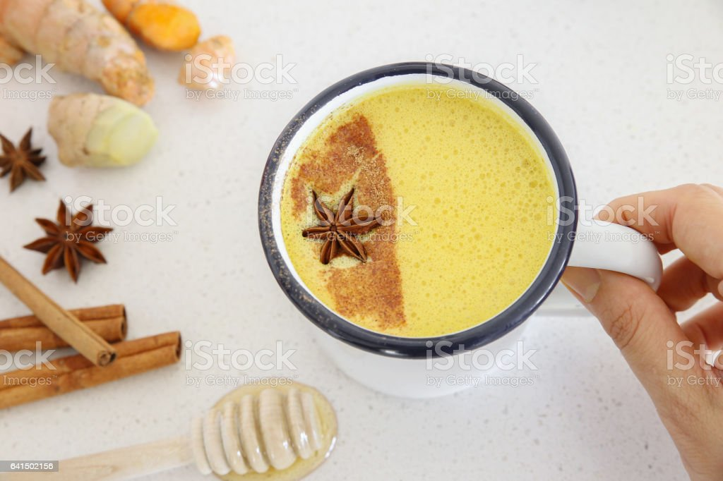 Turmeric latte, Golden milk, Turmeric milk made from turmeric, almond mink, cinnamon, ginger and honey, healthy hipster drink stock photo