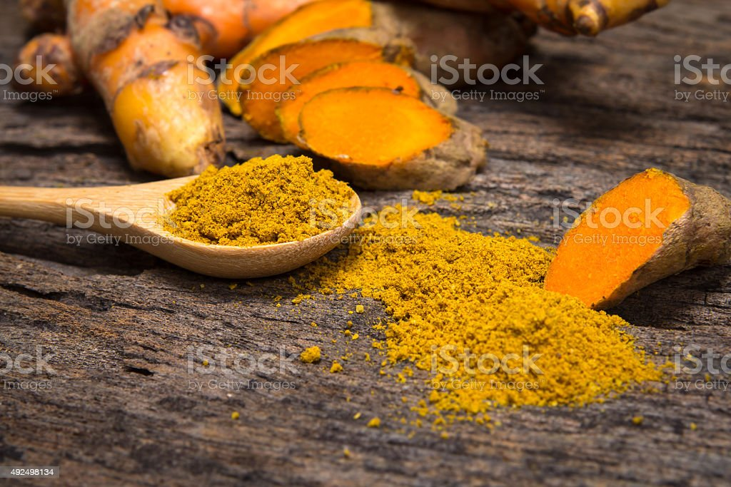 turmeric powder in spoon and roots on wooden plate stock photo