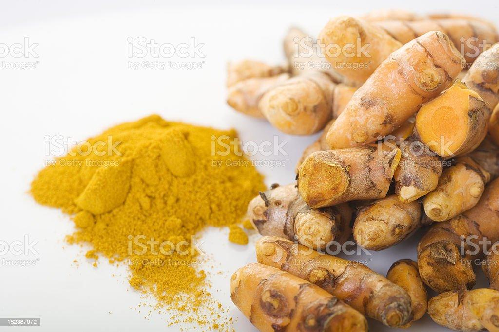 Turmeric powder next to pile of turmeric stock photo