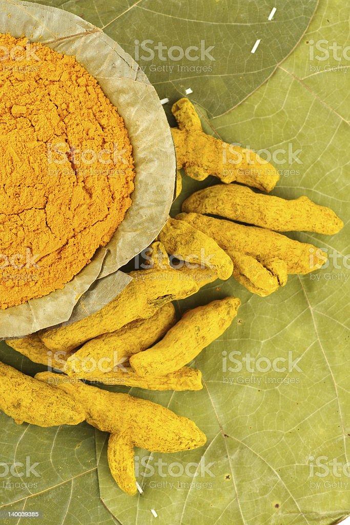 Turmeric roots next to bowl of turmeric powder royalty-free stock photo