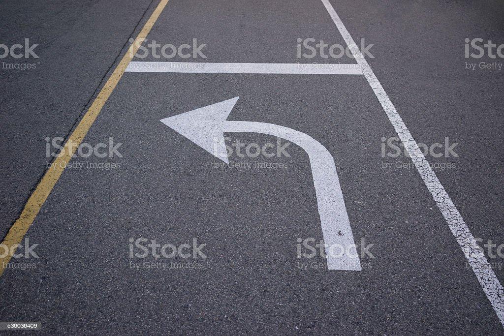 Turn arrow sign on asphalt. stock photo