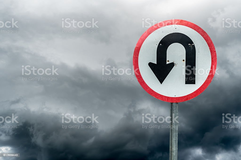 U turn sign on white dark cloud background stock photo