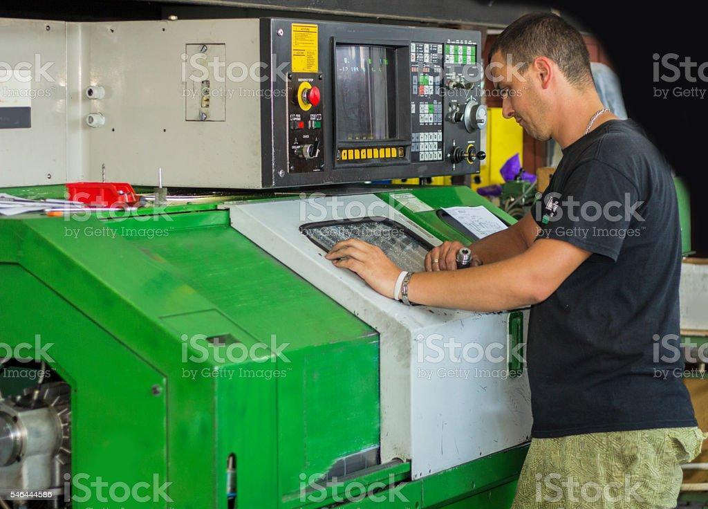 CNC turning machine operator at tool workshop. stock photo