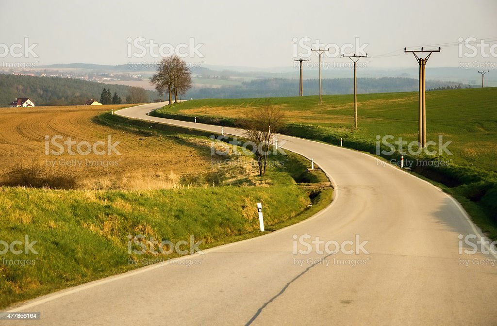 Turning on a small road in sunset rural landscape stock photo