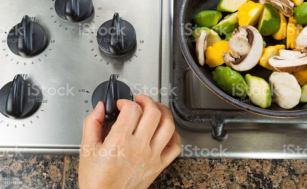 Turning on natural gas stove to cook vegetables stock photo